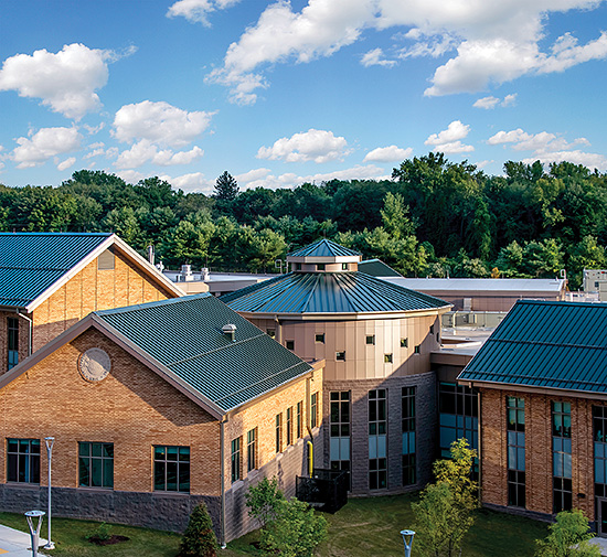 The versatility of metal roofing panels is displayed in Perkins Eastman's design on the International Magnet School which features a circular, segmented Snap-Clad metal panel roof surrounded by connecting rectangular pitched structures.