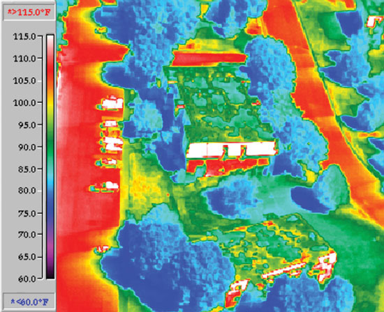 When these two images were created, the outside temperature was 83 degrees Fahrenheit. The top green square in the infrared image shows the temperature of a white membrane cool roof: 89 degrees Fahrenheit. The middle red square shows the temperature of a BUR roof: 115 degrees Fahrenheit. And the red showing the temperature of the asphalt road and parking is 108 degrees Fahrenheit.