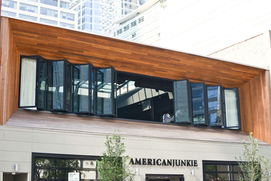 An expanse of folding glass windows admits natural light that adds to the appeal and energy efficiency at American Junkie restaurant.