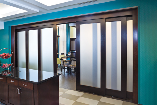 Telescoping door systems smoothly retract and extend multiple door panels moving in the same direction, providing an elegant barrier solution for large openings.