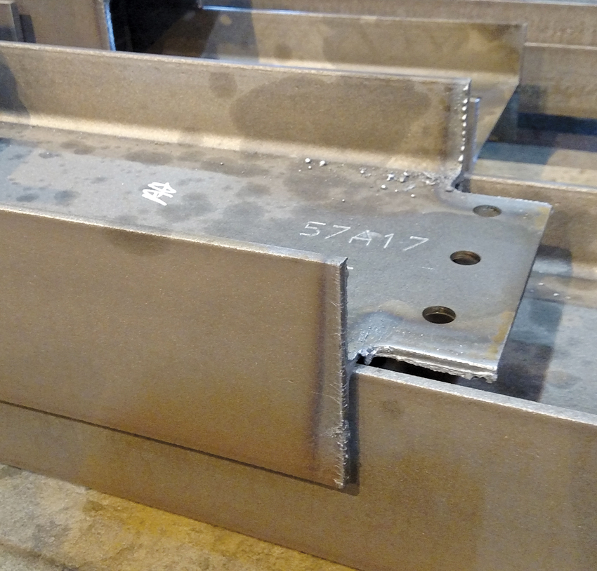 Pictured is a steel beam, recently cut to size and the ends coped per the standard requirements of the AISC Code of Standard Practice for structural steel. The edges have not been ground smooth. Etched numbers and heat marks are visible from the fabrication process. This member is not specified to meet AESS finishes.