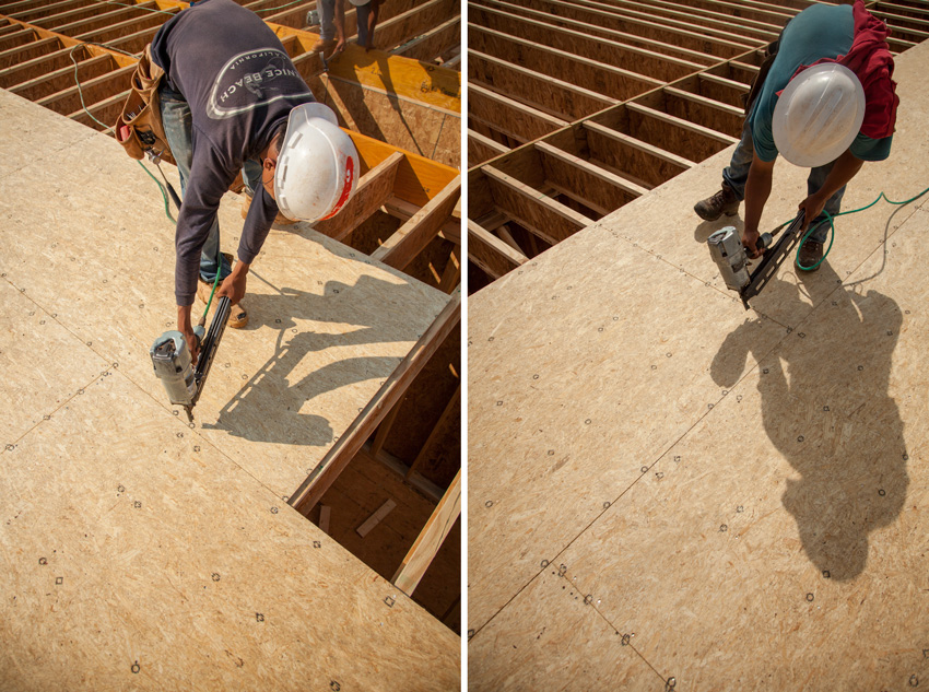 Photo of workers applying screws in preprinted marks on subfloor panels.