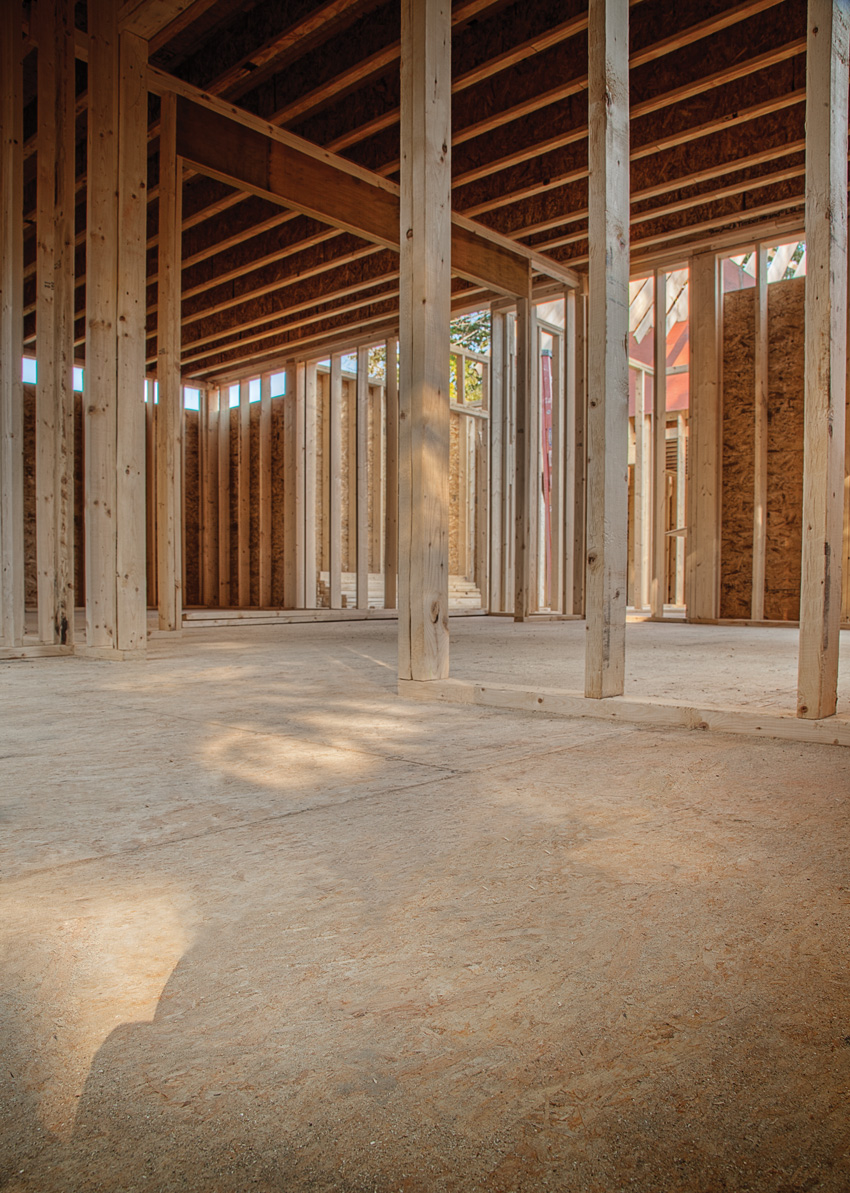 Photo of an interior with wood floors under construction.