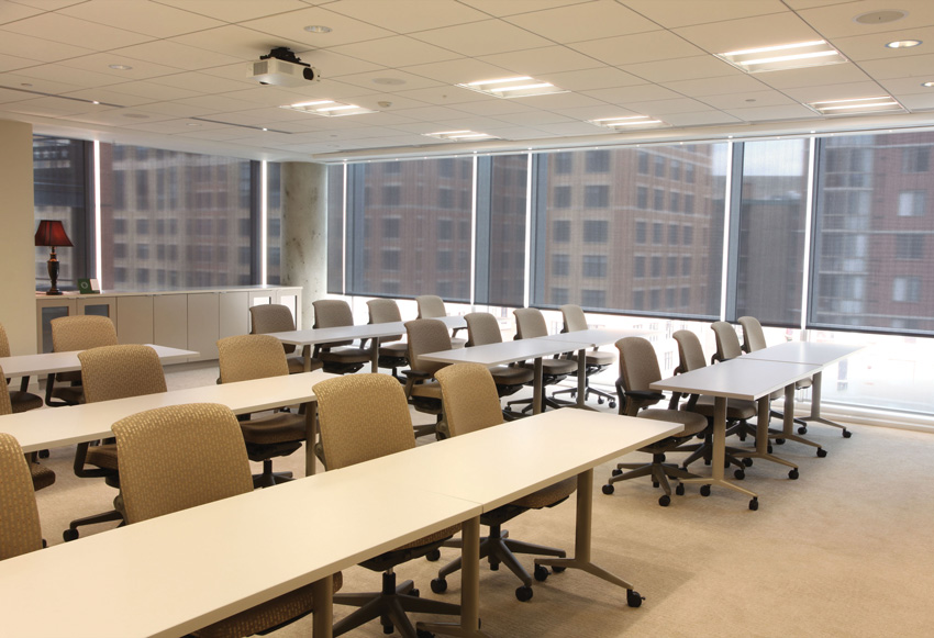 Photo of a lecture room interior with solar shade fabric on the windows.