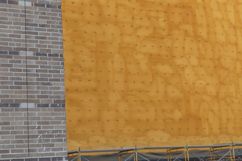 Photo of a large exterior wall covered with a continuous, joint-free layer of spray foam insulation.