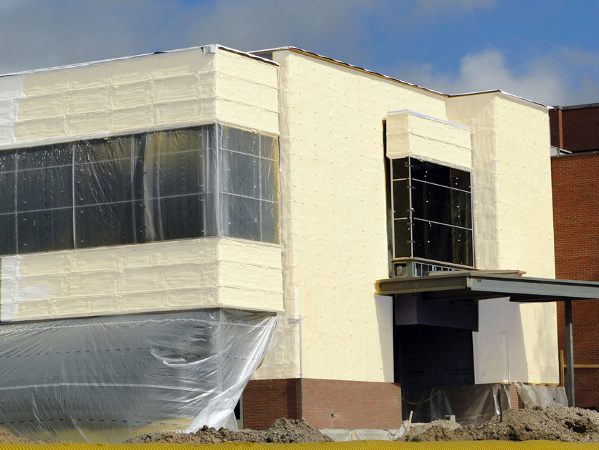 Photo of a building under construction with continuous spray foam insulation along its exterior walls.