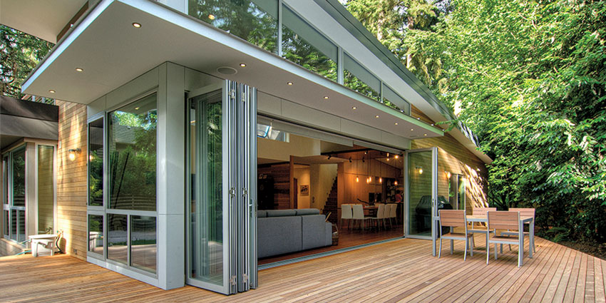 Multi-panel door systems eliminate barriers between interior and exterior spaces, creating a natural and open flow. Aluminum thermally broken folding doors showcase the beauty of surrounding landscaping at this home.