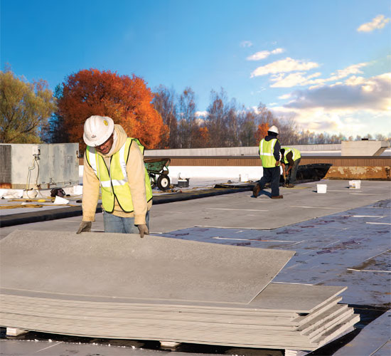 For a relatively small cost, roofing cover board protect the roofing insulation and membrane from the negative forces of fire, wind uplift, impact and hail, moisture, sound intrusion and foot traffic. Above, workers lay out 1/4