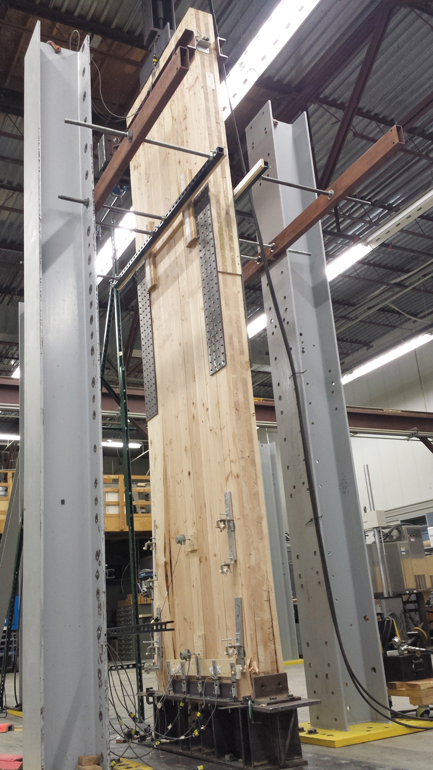 In this rocking test of a CLT shear wall, the panel maintained its lateral load-bearing strength under cycling loading to simulate seismic conditions and returned to a vertical position at completion of the test.