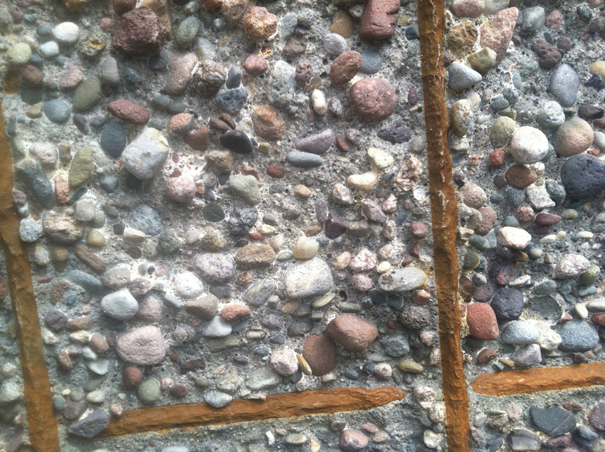 Photo of rusted steel embedded in concrete.