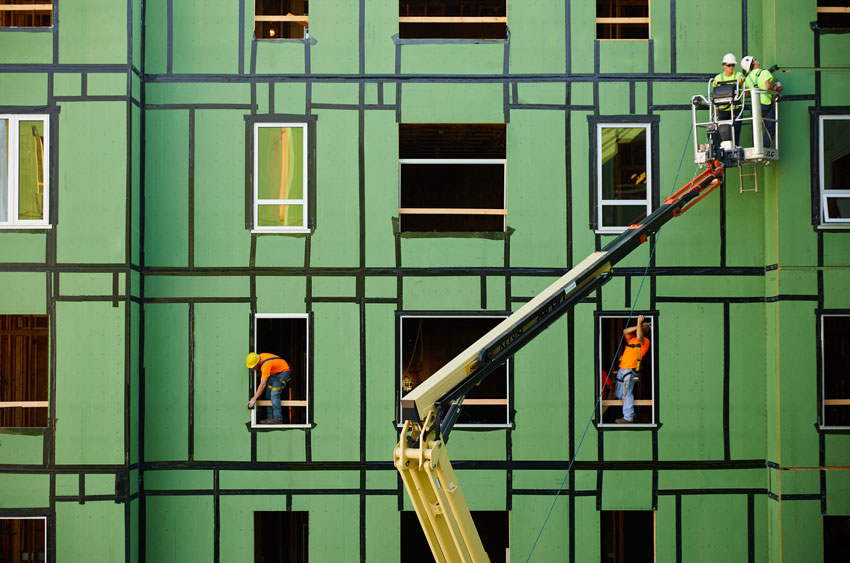 Green building with construction workers for building enclosures