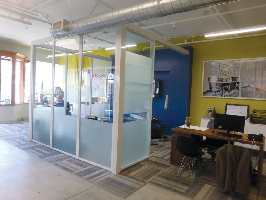 Photo of an office with glass enclosures.