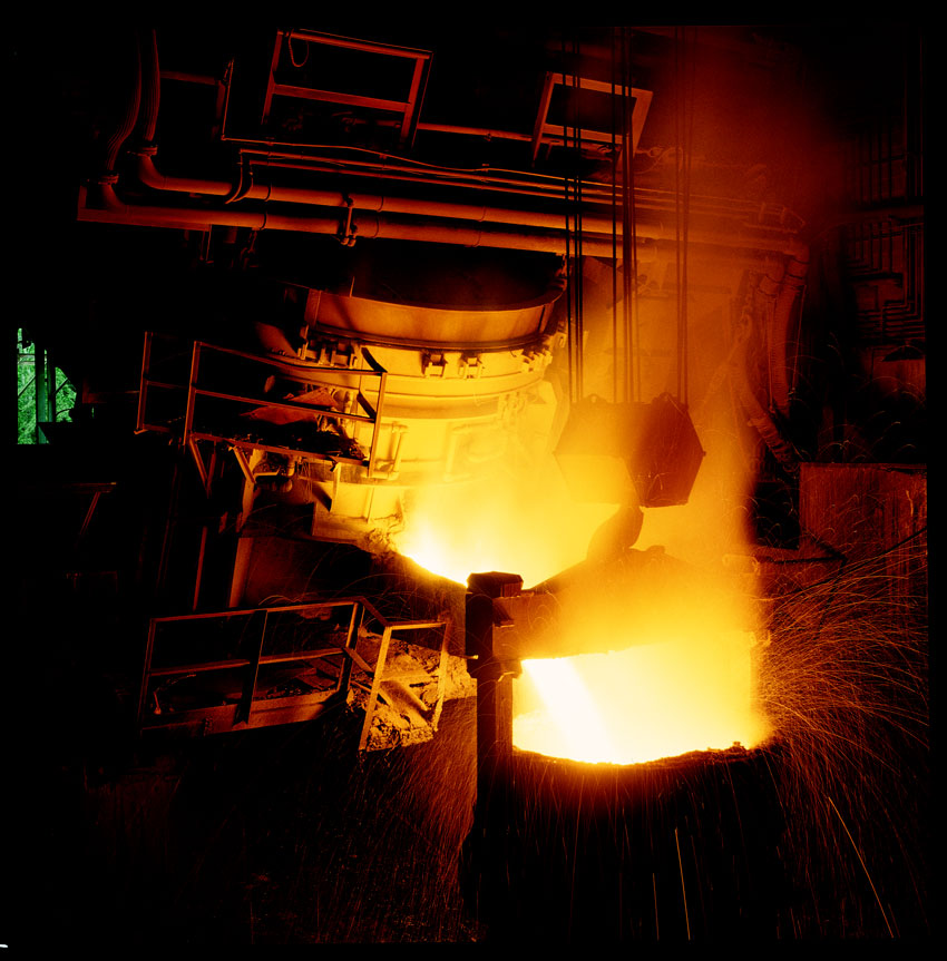 Shown is an electric arc furnace discharging molten steel into a ladle.