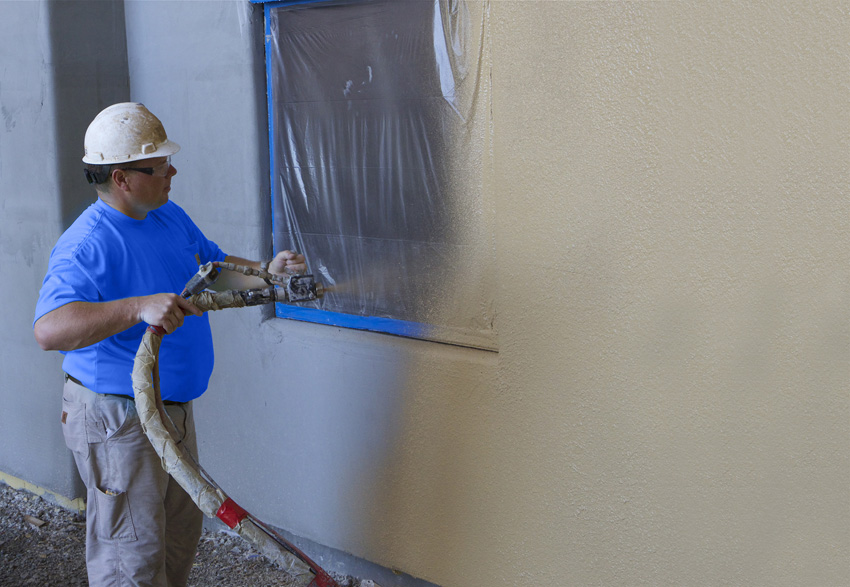 Photo of a man applying stucco with a pump.
