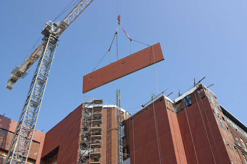 Lightweight concrete panels being lifted in place using equipment designed for this tight site footprint