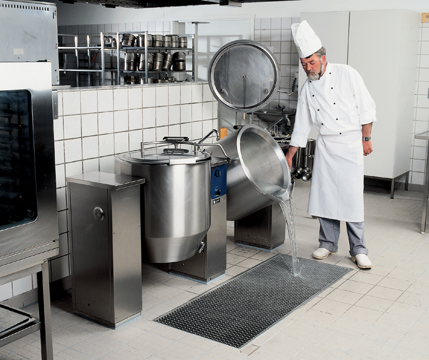 a chef pouring out water down the stainless steel drainage system